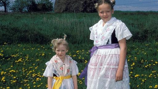 Kinder in einer Tracht stehen auf einer sommerlichen Blumenwiese., Quelle: IMAGO